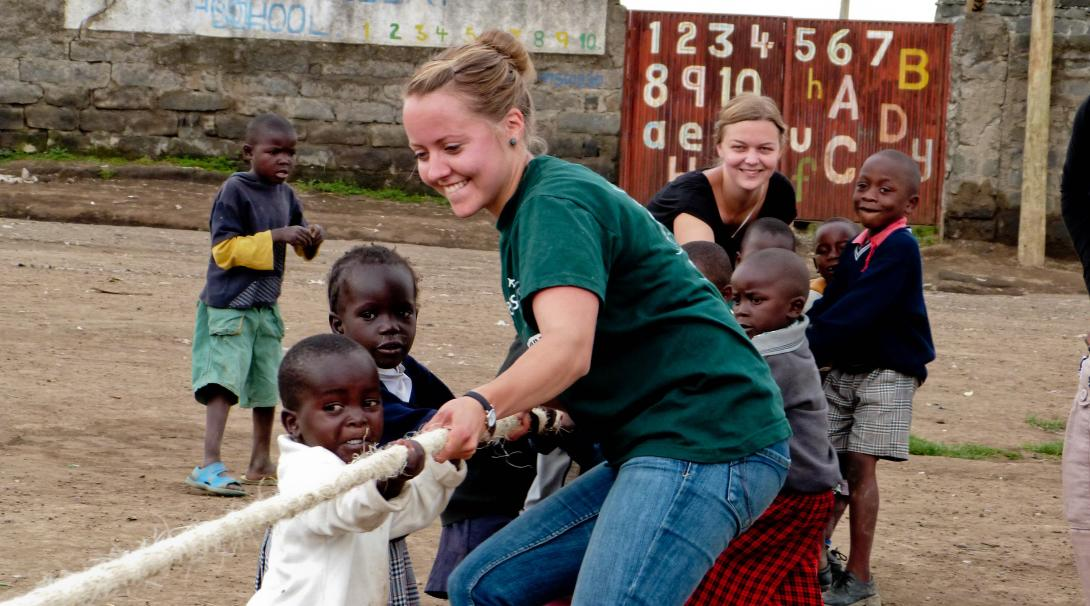 Volunteers working with children in Ghana teaches them teamwork with a fun activity.